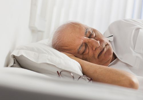 An older man sleeping in his bed with his glasses next to him