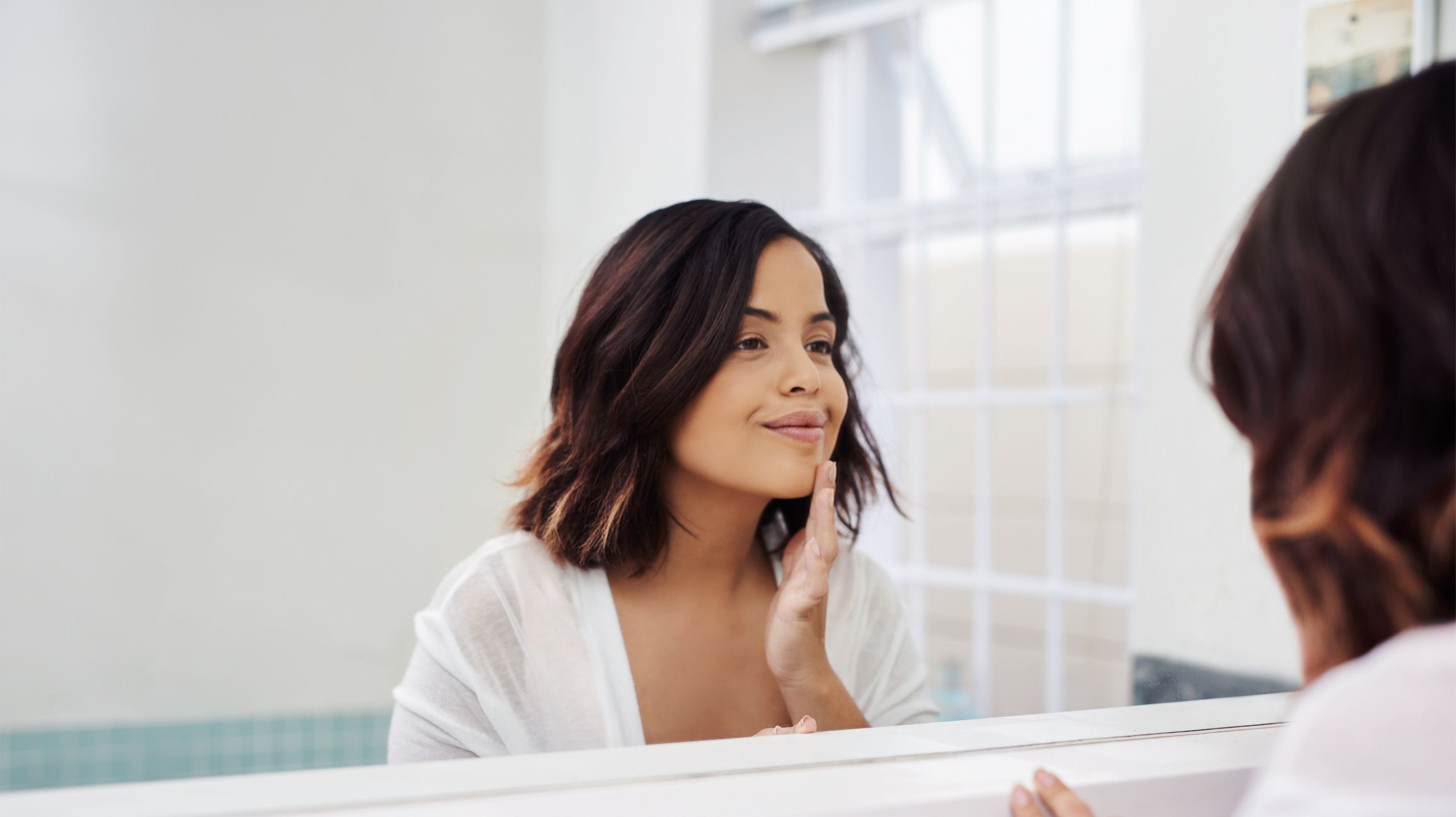Woman looking in the mirror at her skin