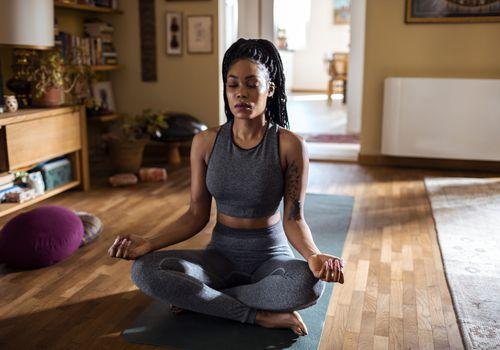 A Black woman meditating at home
