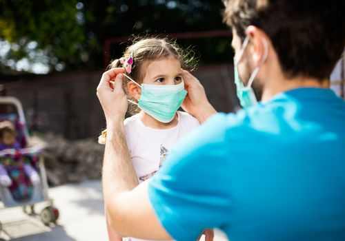A man putting a face mask on a small female child.