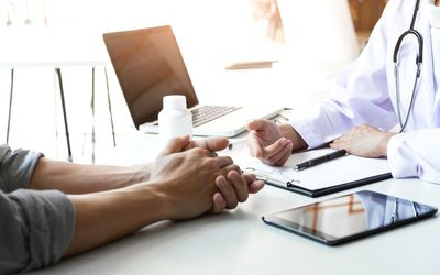 Patient clasped hands talking to doctor