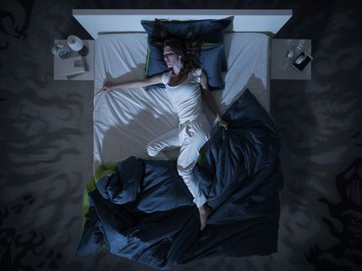 A high-view photograph of a woman in white pajamas in her bed, her covers are pushed down to the bottom and she looks uncomfortbale.