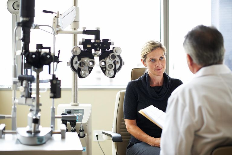 woman talking to eye doctor in exam room