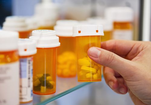Pills on medicine cabinet shelf.