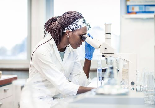 A Black woman scientist in a lab looking in a microscope.
