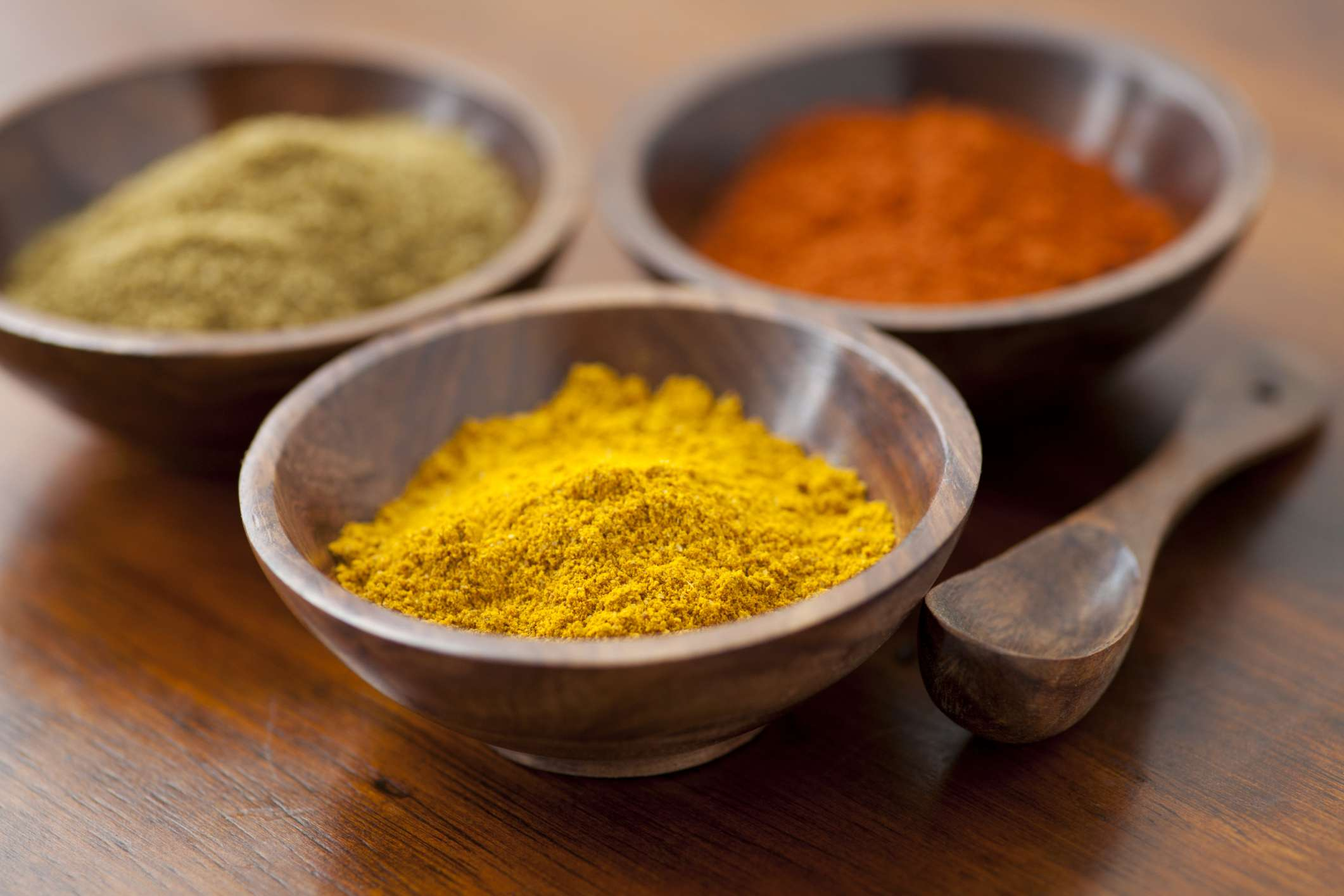 Small wooden bowls of spices including turmeric