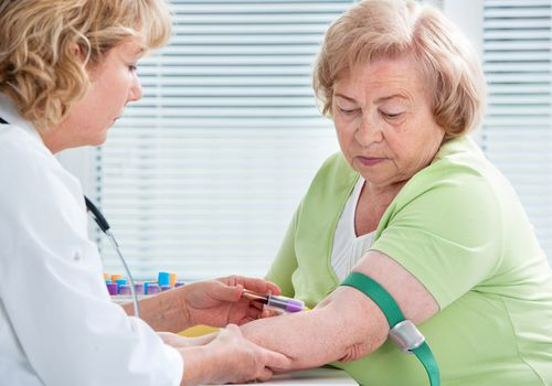 Older woman getting blood drawn by a phlebotomist