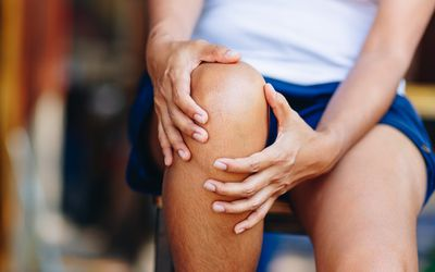 Midsection of woman with knee pain sitting on chair