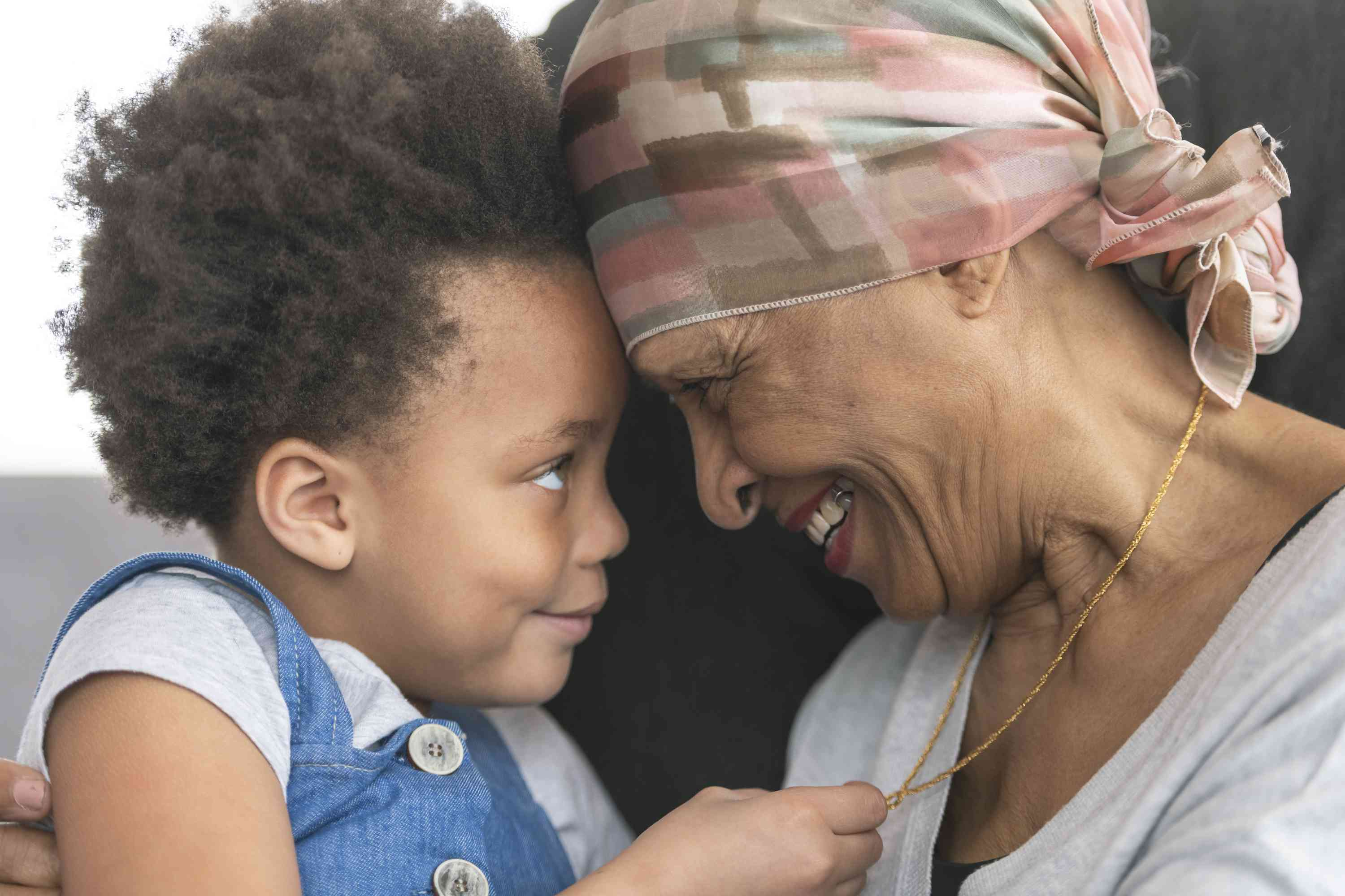 A black woman with cancer is wearing a scarf on her head smiling at her young grandchild.