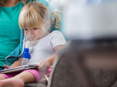 Sad little girl receives breathing treatment at home
