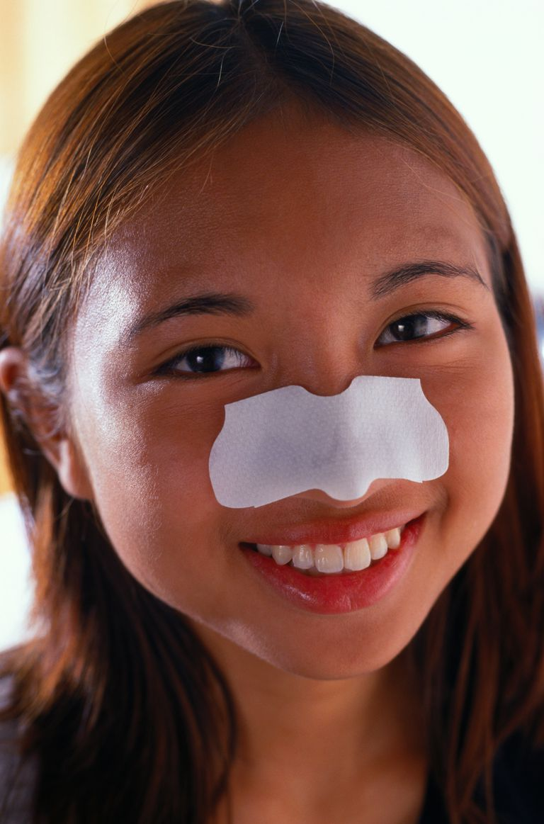Young lady with pore strip on her nose.