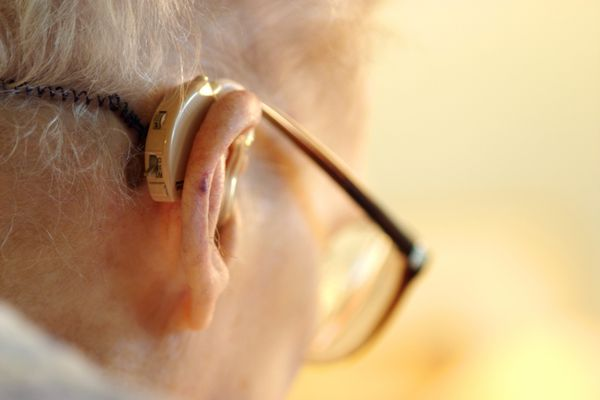 An older man with hearing aids looking down