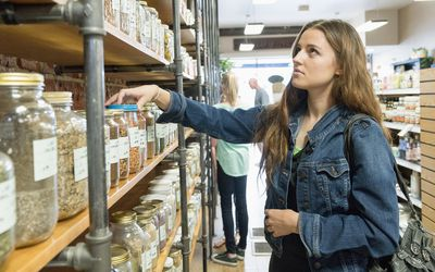 Woman in nutrition store comparing grain products on shelves looking anxious