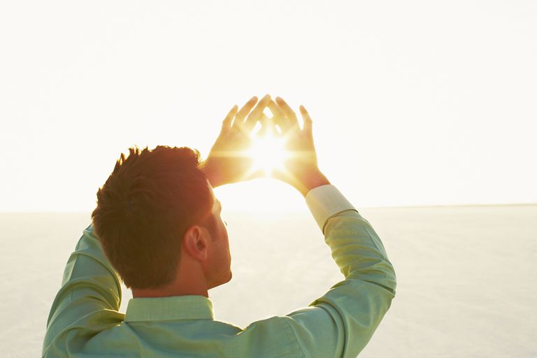 Man framing the sun with his hands