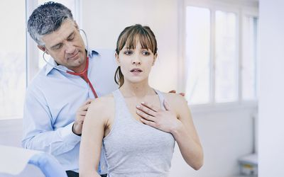 A doctor checks a patient with breathing problems.