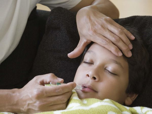 Father taking temperature of sick son
