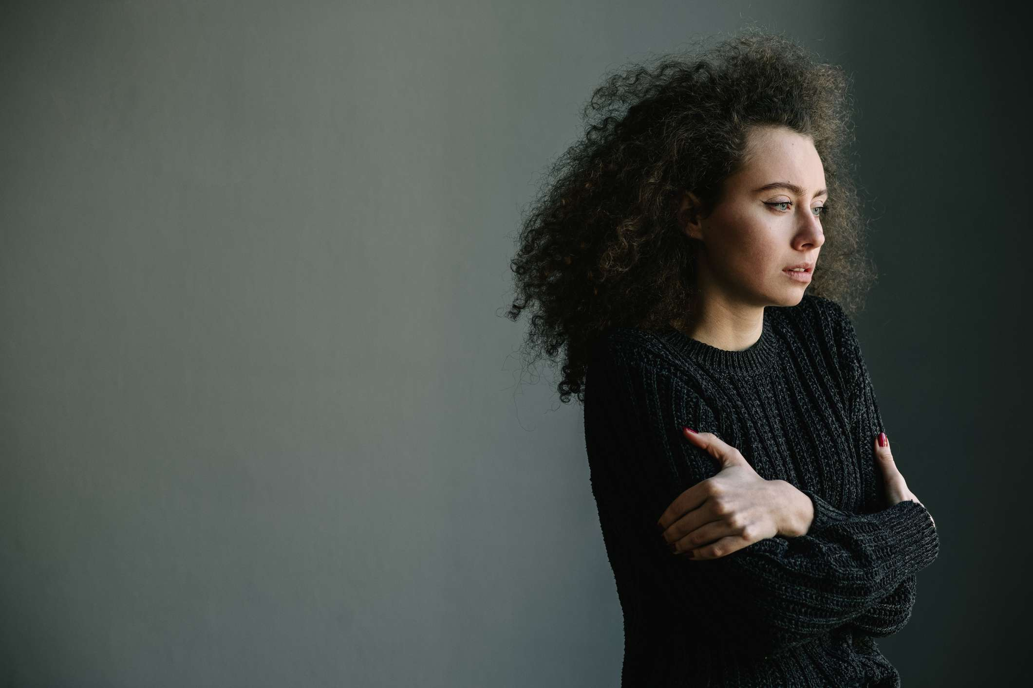 Woman holds hugs herself and stares off to her left with gray background
