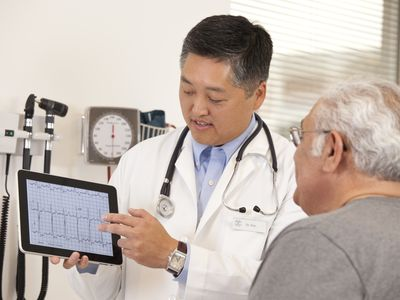 Doctor showing patient ECG results on a tablet