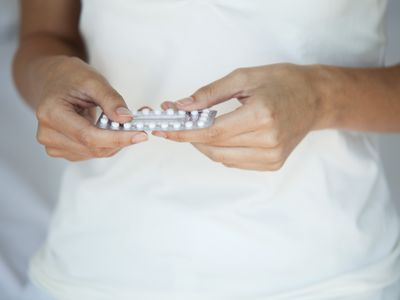 Woman holding birth control pills, mid section