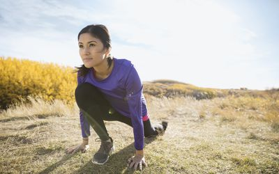 A runner stretching in a sunny field