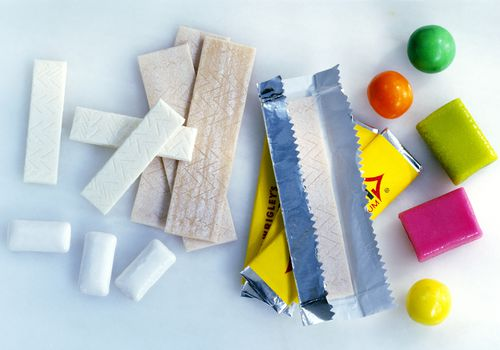 Assorted types of chewing gum on background