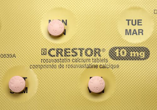 Three Crestor pills sitting on their blister pack