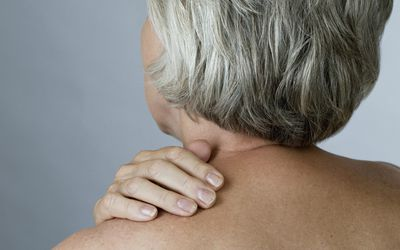 Senior woman with shoulder tension or back ache