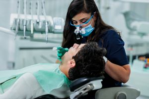 Dentist performing oral surgery