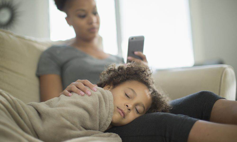 Child wrapped in blanket sleeps in mother's lap
