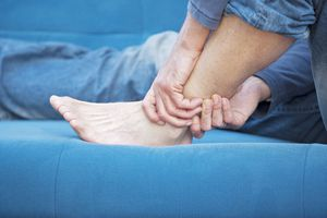 A man rubbing his hurt ankle