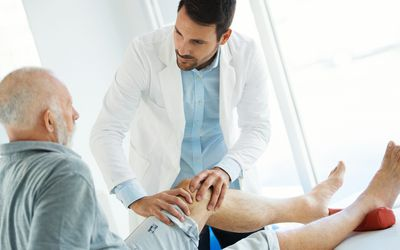 Senior man having his knee examined