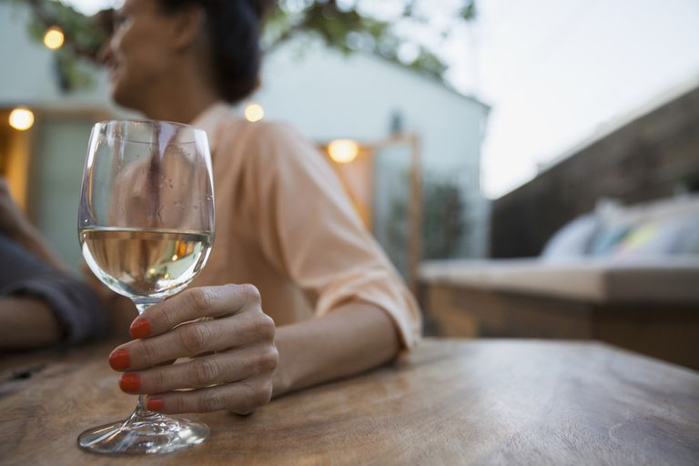 Woman drinking white wine on patio