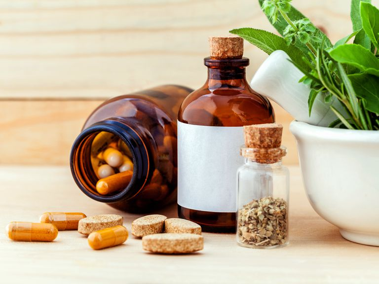 Closeup of herbal supplements and herbs in apothecary bottles