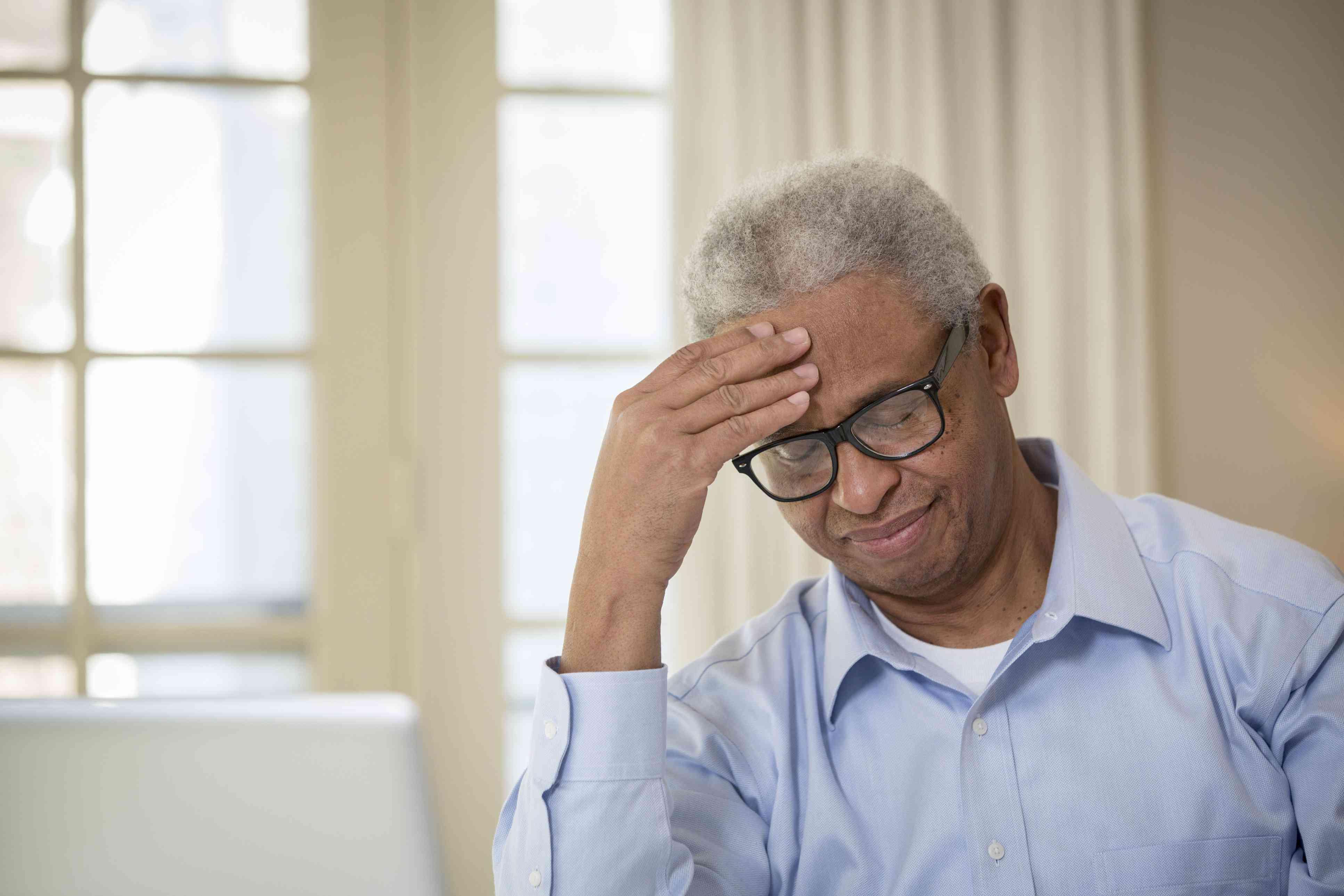 Older man rubbing his forehead