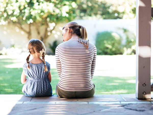Mother and daughter sitting on a porch talking