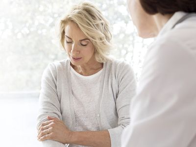 Mature woman showing medical professional her painful arm
