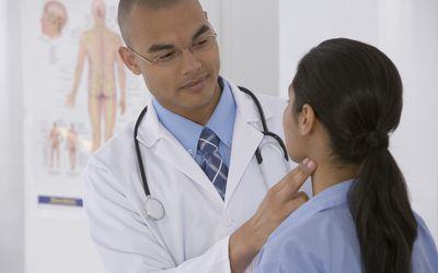 Doctor taking a woman's pulse via the carotid artery