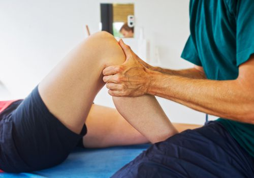Physical therapist massaging patients knee