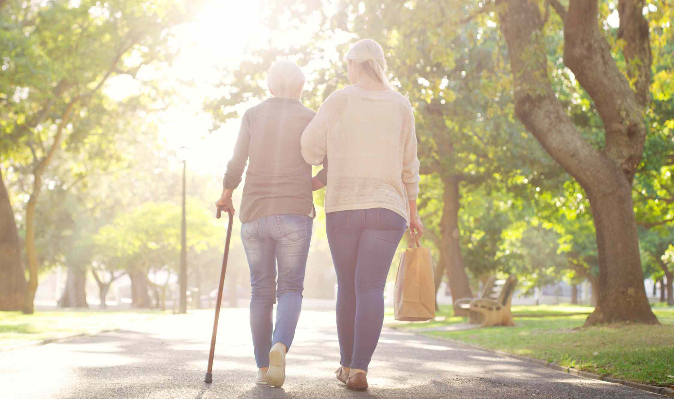 Mother and daughter walking in the park. Older woman is using a cane.