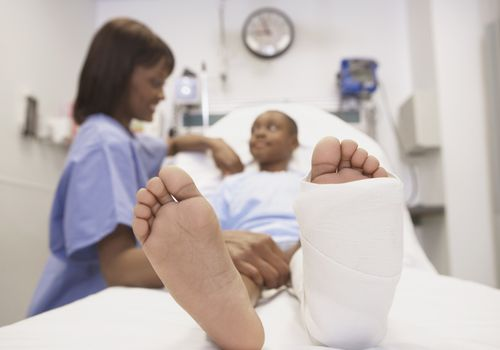 Photo of a nurse comforting patient with a broken foot.