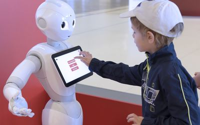Little boy interacts with touchpad on a robot's chest