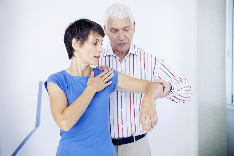 woman with shoulder pain being evaluated by a doctor