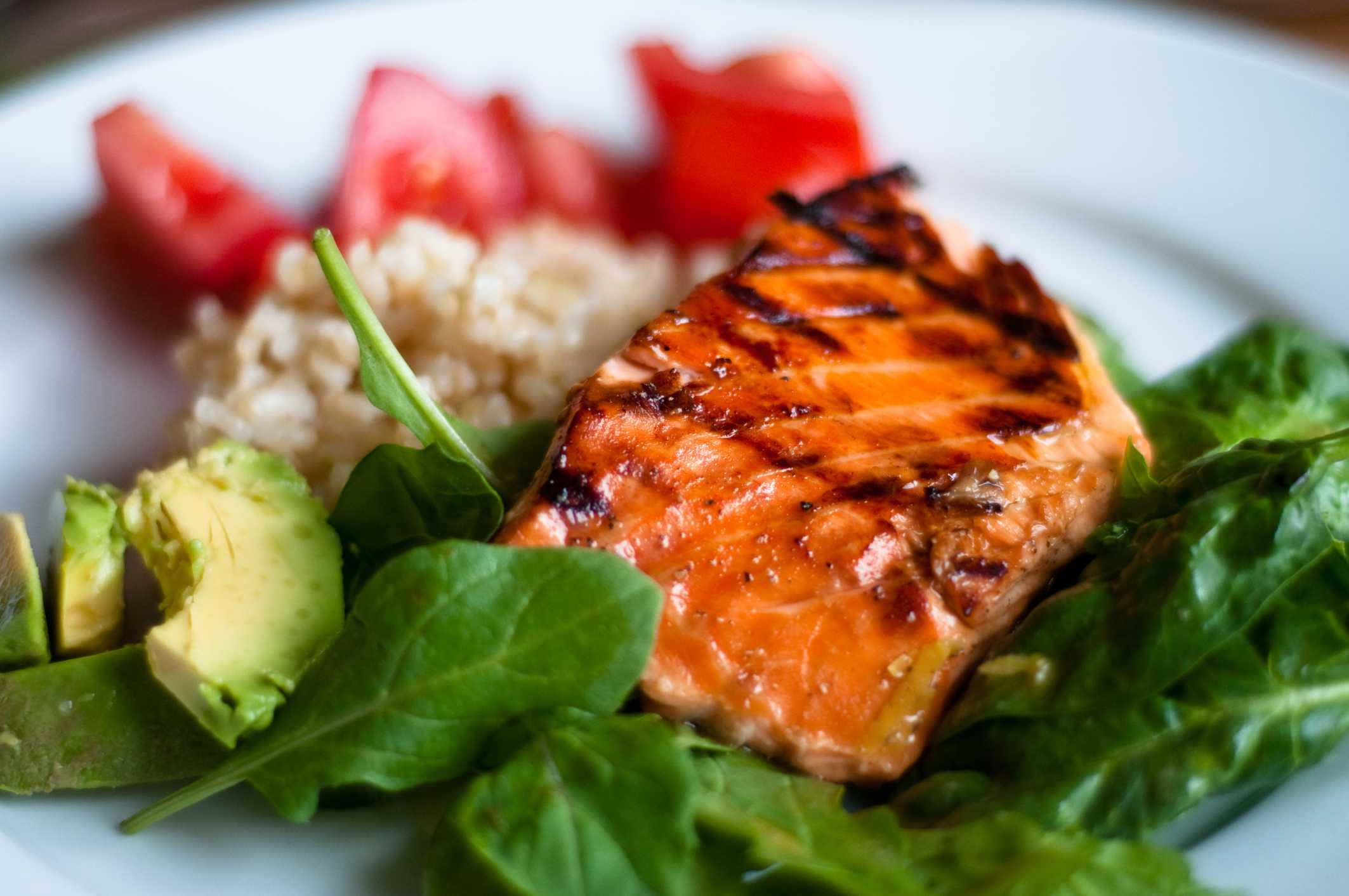 cooked salmon on a bed of spinach with sides of avocado, rice, and tomatoes