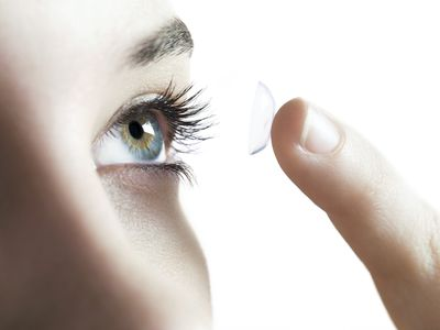 Woman putting on contact lens
