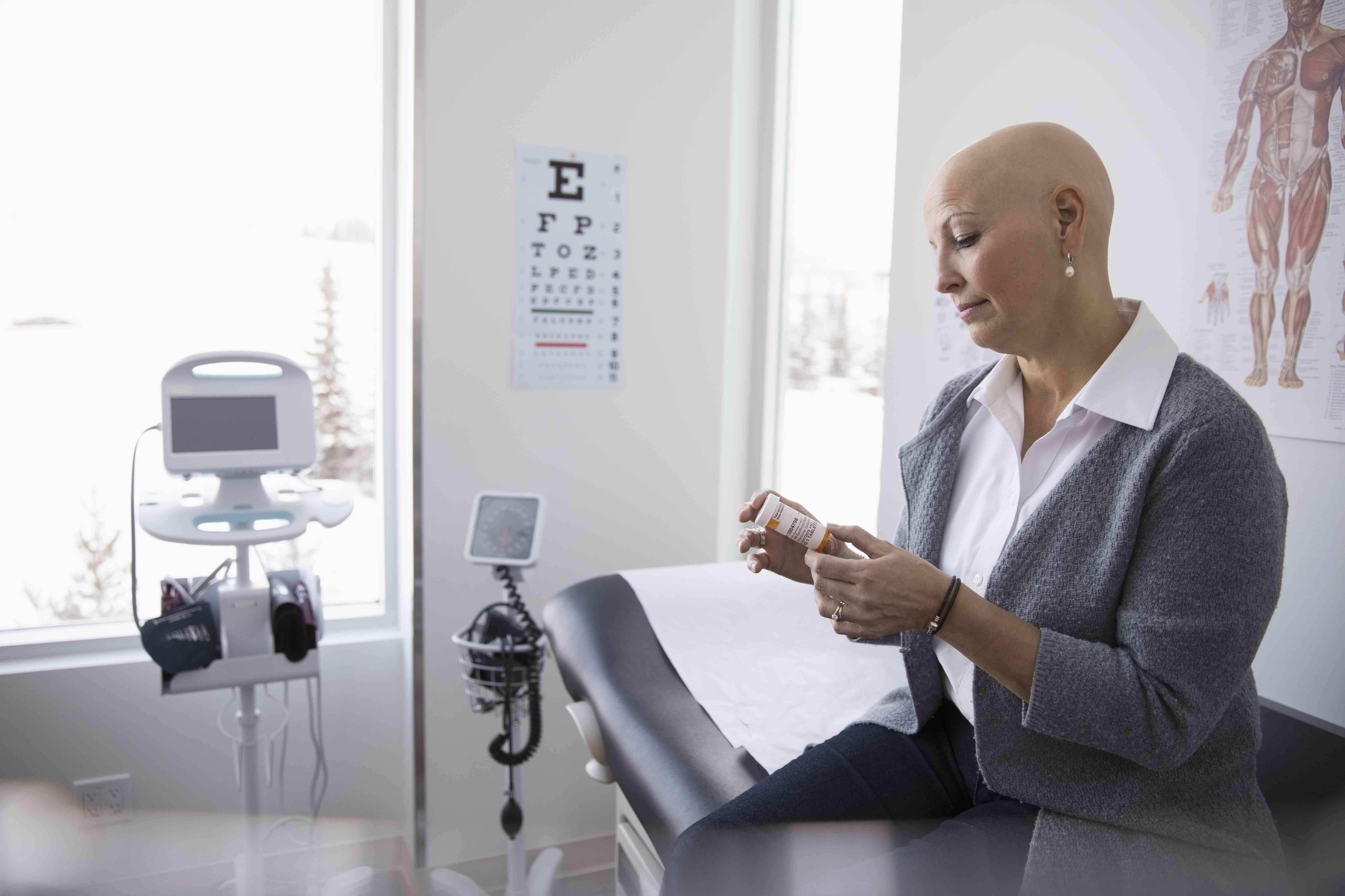 A cancer patient reading label on prescription bottle