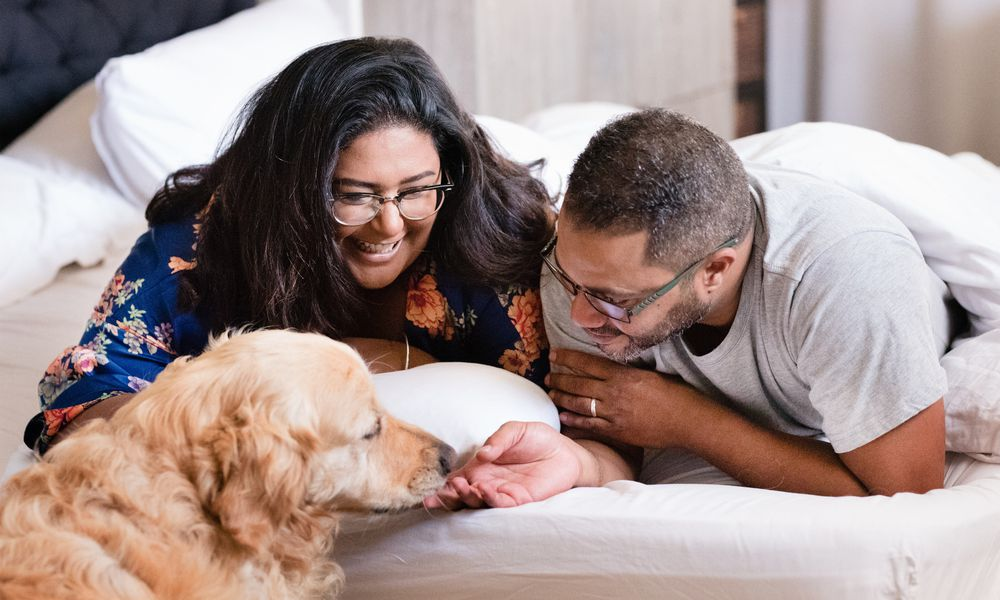 Shot of a middle aged couple in bed with their dog in morning