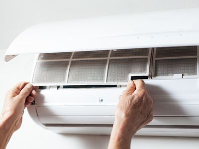 A person changing the filter on an air conditioner.