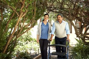 a nurse walking with a man with a walker