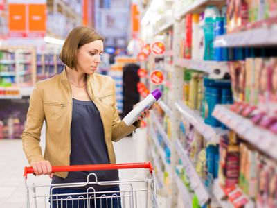 woman looking at dandruff shampoos in store aisle