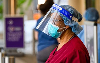 Medical worker wears face shield and surgical mask outside of NYU Langone